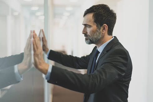 Thoughtful mature businessman leaning against glass wall in office - MOEF02552