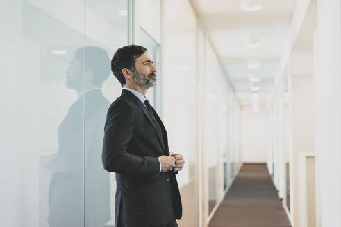 Thoughtful mature businessman leaning against glass wall in office - MOEF02555