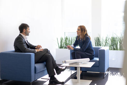 Businesswoman and businessman sitting in armchairs in office talking - MOEF02561
