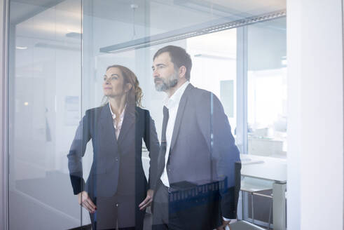 Businesswoman and businessman in office looking through glass pane - MOEF02576