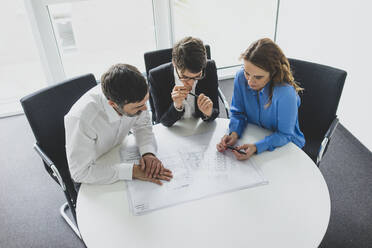 Businessman and two businesswomen working on plan on desk in office - MOEF02594