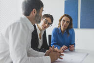 Businessman and two businesswomen working on plan on desk in office - MOEF02597