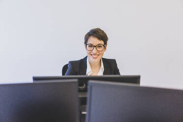 Portait of smiling young businesswoman at desk in office - MOEF02630