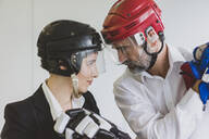 Businesswoman and businessman wearing ice hockey equipment in office - MOEF02636