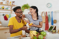 Multiethnic couple breakfasting together in the kitchen - IGGF01399