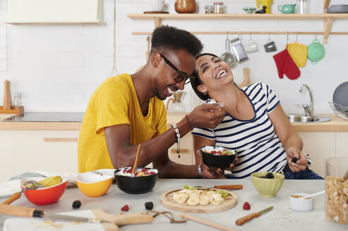 Multiethnic couple laughing, breakfasting together in the kitchen - IGGF01408