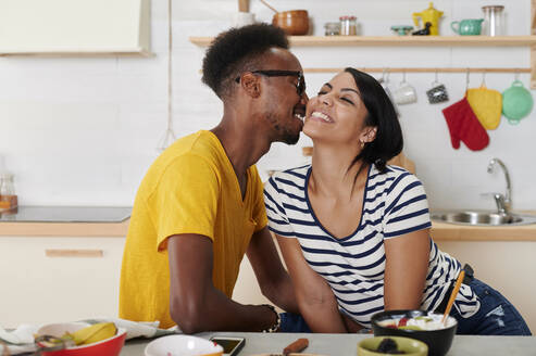 Multiethnic couple breakfasting together in the kitchen - IGGF01411