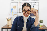 Young smiling woman with hand on glasses - IGGF01423