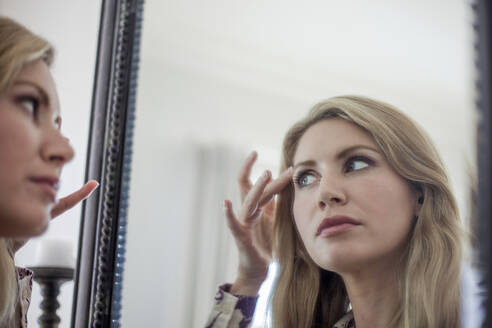 Woman checking make up in a mirror - AJOF00044