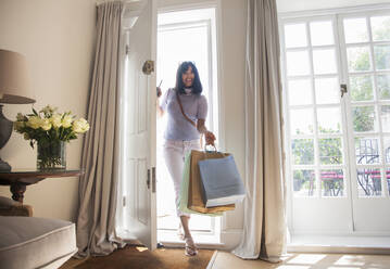 Woman with shopping bags, coming through front door - AJOF00050