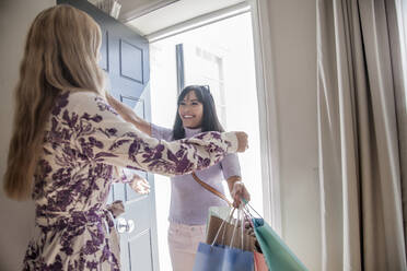 Woman with shopping bags visiting friend at home - AJOF00053