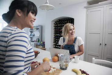 Two friends preparing fresh smoothie, chopping fruits in the kitchen - AJOF00068