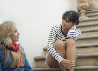 Two women chatting, sitting  on steps - AJOF00074