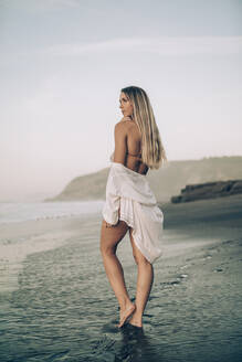 Young blond woman wearing bikini and white dress at the beach in the morning - MTBF00114