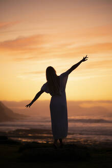 Silhouette of young woman during sunrise at the beach - MTBF00126