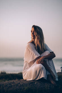 Young blond woman sitting at the beach and looking sideways during sunrise - MTBF00129