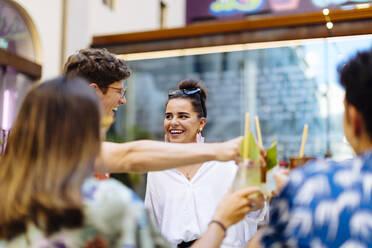 Happy multi-ethnic friends toasting drinks - SODF00156