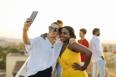 Young women taking a selfie during a party in the evening - SODF00174