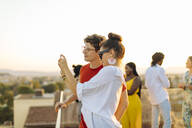 Young woman and man taking a selfie during a party in the evening - SODF00177