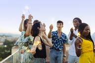 Group of happy multi-ethnic friends celebrating a party in the evening, holding sparklers - SODF00186