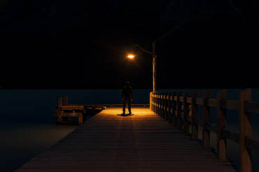 Rear view of a man standing on pier at night - SMAF01659