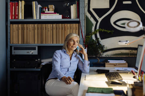 Mature woman working in architct's office, talking on the phone - SODF00210