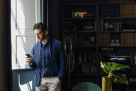 Man standing in his office, using smartphone - SODF00234