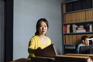 Young woman looking at files in office - SODF00264