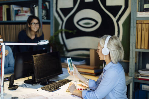 Mature woman talking on the phone with headphones, sitting in architect's office - SODF00270