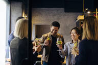 Colleagues celebrating after work in a bar - SODF00276