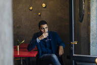 Young man relaxing with an after work cocktail - SODF00288