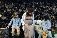 Pregnant mother with two kids and dog relaxing at stack of wood - SODF00315