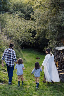 Rear view of family with two kids walking in the countryside - SODF00318