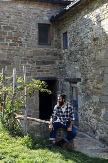 Man with beard sitting on a wall at a rustic farmhouse - SODF00324