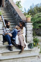 Family relaxing on stoop of a rustic house - SODF00327