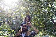 Father with kid on his shoulders in an orchard - SODF00330