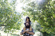 Portrait of father with kid on his shoulders in an orchard - SODF00333
