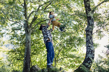 Father lifting up kid in the forest - SODF00345