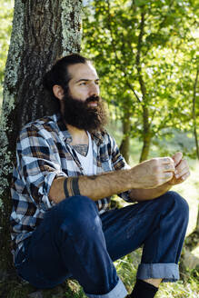 Man with beard sitting at tree trunk in the forest - SODF00348