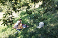 Mother with two kids and dog relaxing in the countryside - SODF00351