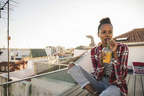 Young woman having a drink on rooftop at sunset - UUF19452