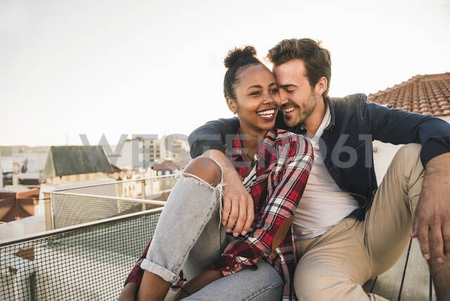 Happy affectionate young couple sitting on rooftop in the evening - UUF19458 - Uwe Umstätter/Westend61