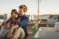 Happy affectionate young couple sitting on rooftop in the evening - UUF19476