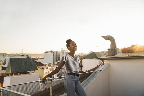 Happy young woman standing on rooftop at sunset - UUF19482