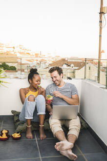 Happy young couple with laptop sitting on rooftop in the evening having a snack - UUF19485