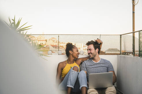 Happy young couple with laptop and earphones sitting on rooftop in the evening - UUF19488