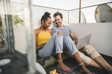 Happy young couple with laptop and earphones sitting on rooftop in the evening - UUF19491