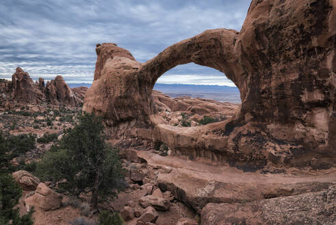 Rock formations at Arches National Park against cloudy sky - CAVF68264