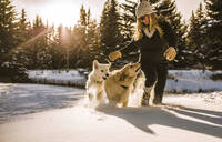 Smiling woman with dogs walking on snow covered field in forest - CAVF68285
