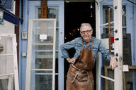 Portrait of senior hardware store owner standing with hand on hip while leaning on door - MASF14029